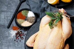 Raw whole chicken, herbs, spices and lemon