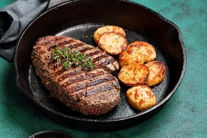 Grilled beef steak and potato in cast iron skillet