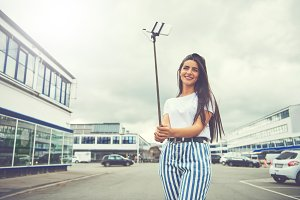Pretty woman in striped pants holding selfie stick