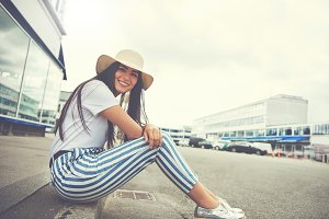Woman seated on curb wearing striped pants