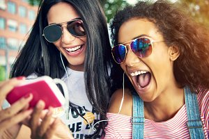 Female friends wearing sun glasses and smile