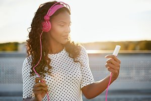 Sunlit woman listening to music