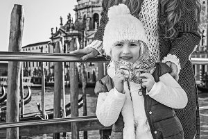 happy mother and child travellers holding Venetian mask, Venice
