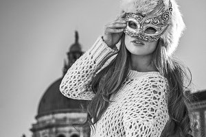 elegant fashion-monger in Venice, Italy wearing Venetian mask