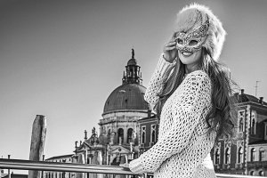 fashion-monger in Venice, Italy looking aside in Venetian mask
