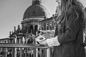 fashion-monger on embankment looking on Venetian mask