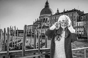 smiling elegant woman in Venice, Italy wearing Venetian mask