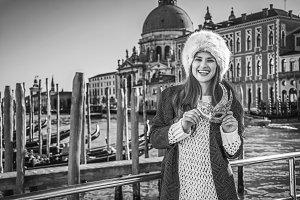 smiling fashion-monger in Venice, Italy holding Venetian mask