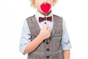 Little boy with red paper heart