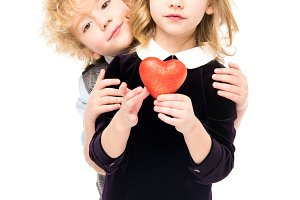 Little kids holding red heart