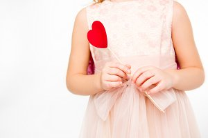 Girl with red paper heart on stick