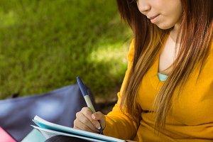 Female college student doing homework in park