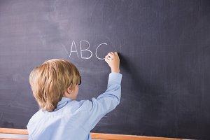 Student writing on large blackboard
