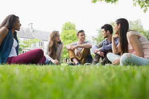 Happy students sitting outside on campus