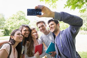 Happy students taking a selfie outside on campus