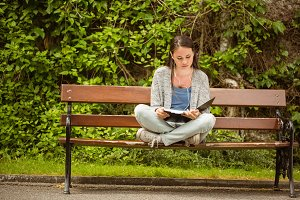 Student sitting on bench listening music with mobile phone and revising