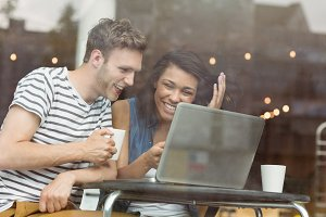Smiling friends with a hot drink using laptop