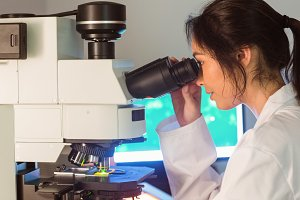 Science student looking through microscope