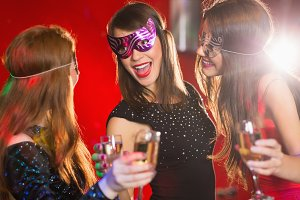 Friends in masquerade masks drinking champagne