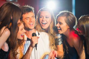 Happy friends singing karaoke together