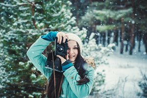 Brunette smiling girl photographed on an old vintage camera in winter forest