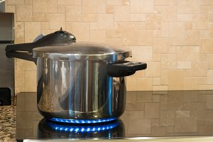 Stainless steel pressure cooker on hob