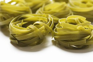 Close-up of vegetable spaghetti on white background. Italian pasta. Horizontal shoot.