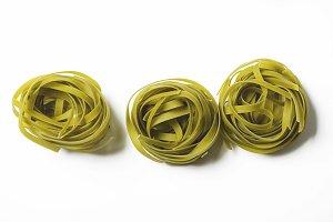 Res rolls of vegetable spaghetti on white background. Italian pasta. Horizontal shoot.