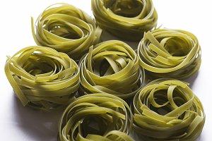 Background of vegetable spaghetti on white background. Italian pasta. Horizontal shoot.