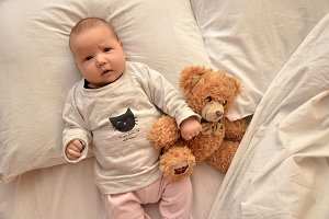 pretty smiling baby girl and teddy bear lying in the bed