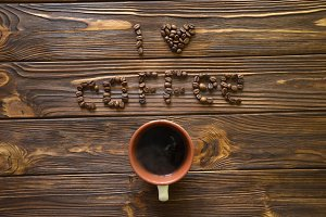 I love coffee written by coffee beans on a wooden table. Coffee written with coffee beans on the table.