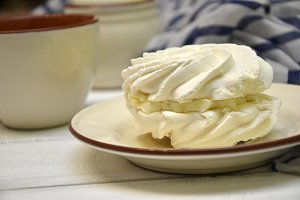 Meringues with a cup on the wooden table.