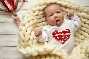 Small child in a blanket of thick yarn. Christmas theme. Happy Valentines Day