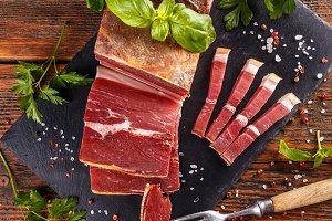 Prosciutto sliced on black slate
