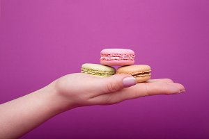 Woman's hand holding macaroons
