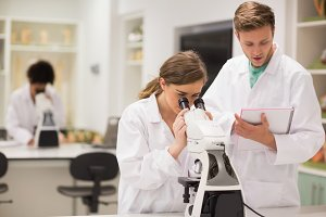 Happy medical students working with microscope