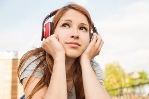 Pretty redhead lying on bench listening to music