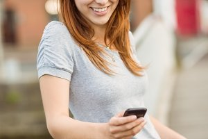 Smiling redhead with her mobile phone texting a message