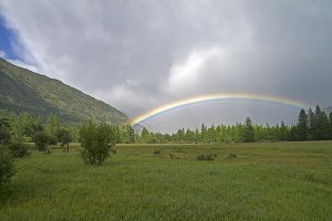 Rainbow in a mountain valley.