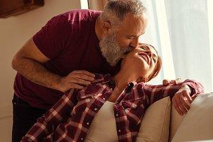 Mature man kissing happy woman