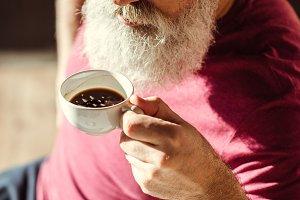 Bearded senior man drinking coffee