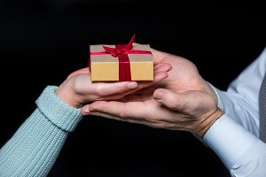 Couple holding gift box in hands