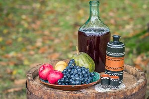 still life on oak barrel of fruit and red wine autumn