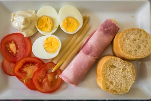 half boiled eggs, sliced tomatoes, bread and ham