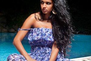 Woman in blue dress posing near pool
