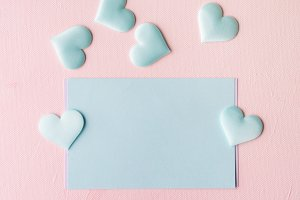 Green pastel card hearts on pink textured background