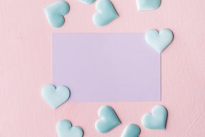 Purple pastel card and hearts on pink textured background