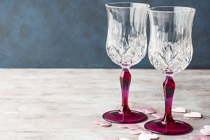 Two pink stemmed champagne glasses and hearts