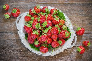 Fresh and delicious organic strawberries on old metal plate, wooden table. Perfect for your healthy eating dieting.