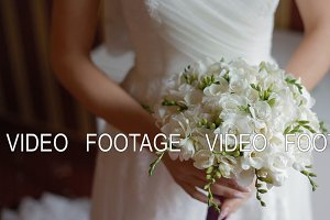 Bride hold wedding bouquet in her arms